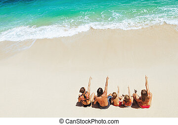 Happy family relaxing on white sand sea beach.