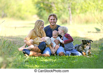 Happy Family Relaxing Outside with Dog