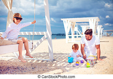 happy family relaxing, playing on beach at summer vacation