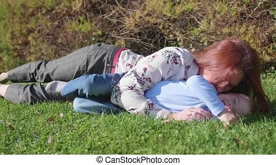 Happy family resting on the lawn.Mother with tenderness and...