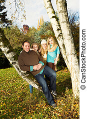Happy Family Resting Outdoors during a nice day in fall season