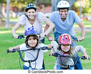 Happy family riding a bike in a park