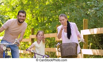 happy family riding bicycles in summer park - family,...