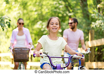 happy family riding bicycles in summer park
