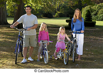 Happy Family Riding Bikes In A Park