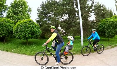 Happy Family Riding Bikes In Green Park Zone