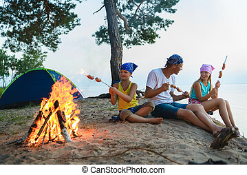 happy family roasting sausages over campfire. camping and tourism concept
