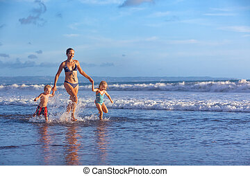Happy family run with fun along sunset beach surf