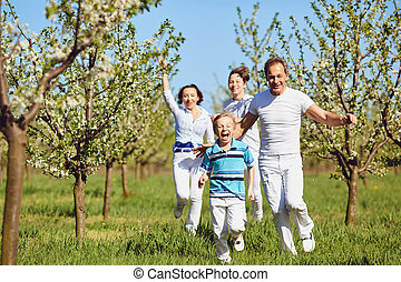 Happy family running in the park in the summer