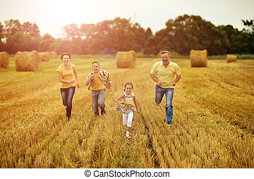 Happy family running on wheat field togrther