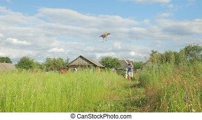 Happy family running with a kite on green grass to the camera. Mother, father and baby 2 years in summer