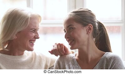 Happy family senior mature mother and young woman talking...