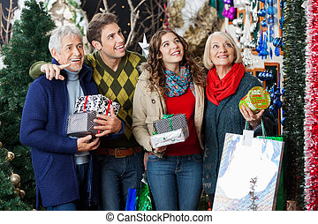 Happy Family Shopping In Christmas Store - Happy family with...
