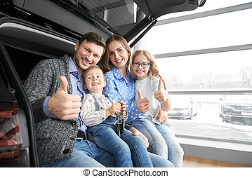 Happy family showing thumbs up, posing in car trunk.