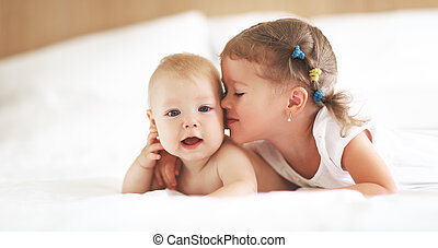 happy family sister kisses baby brother in bed
