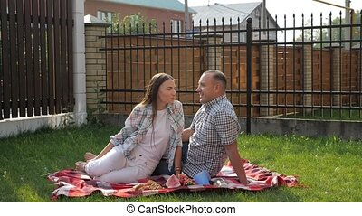 happy family sit on blanket and boy runs hugging parents