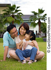 Happy family sits on grass field