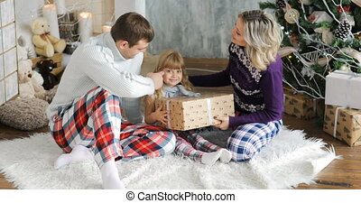 Happy family sitting at floor with christmas gifts A child enjoys a Christmas gift.