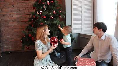 happy family sitting by the christmas tree