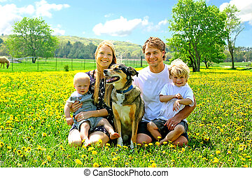 Happy Family Sitting In Dandelion Field