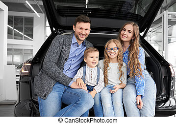 Happy family sitting in luggage space of car, posing.