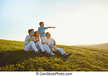 Happy family sitting in nature at sunset in the sun.