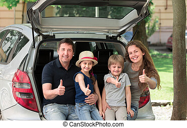happy family sitting in the trunk of a car and showing thumbs up