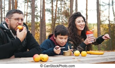 Happy family sitting near to each other outdoors in the woods at the table and enjoy meal.