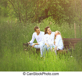 happy family sitting on a bench in the Park in summer Sunny day.