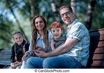 happy family sitting on bench in summer Park