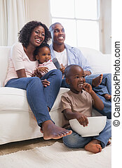 Happy family sitting on couch together watching tv at home...