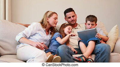 Happy family sitting on couch using tablet pc