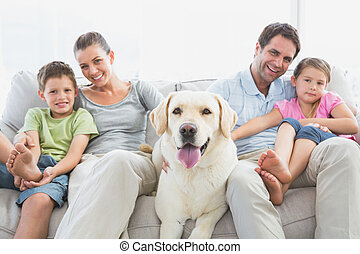 Happy family sitting on couch with their pet labrador at...