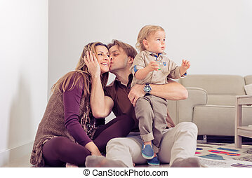 Happy family sitting on floor with their little baby. Family spending time at home with their son. Father kissing a mother.