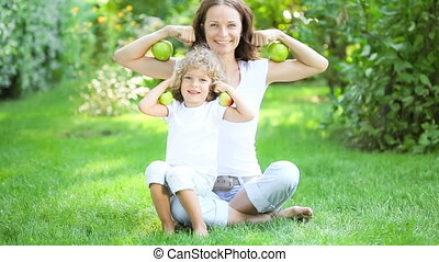 Healthy eating concept - Happy family sitting on green grass...