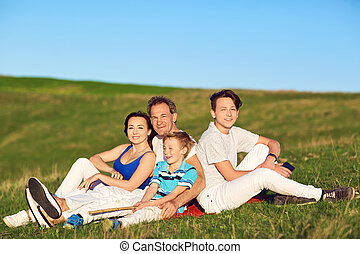 Happy family sitting on nature in spring, summer.
