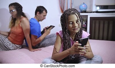 Happy family sitting on sofa and using smartphone laptop. girl mobile phone and digital tablet at home lifestyle