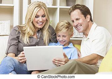 Happy Family Sitting on Sofa Using Laptop Computer