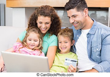 Happy family sitting on sofa using laptop together to shop online at home in living room