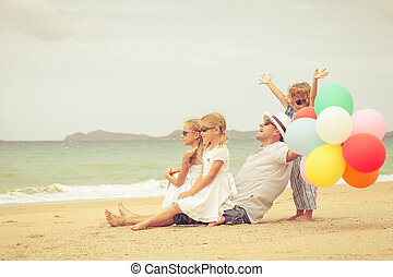 Happy family sitting on the beach at the day time.