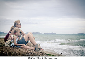 Happy family sitting on the beach at the day time. - Mother ...