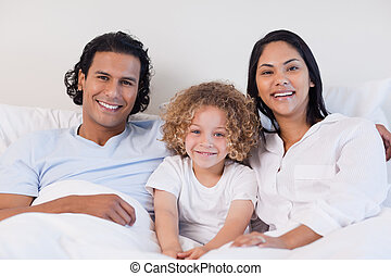 Happy family sitting on the bed together