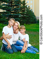 Happy family sitting on the grass in summer. Picnic concept