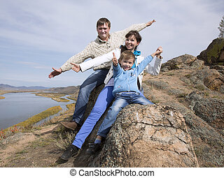 happy family sitting on the stone and showing thumb