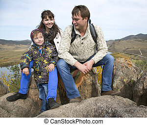 happy family sitting on the stone
