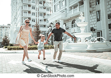 Happy family skipping along the street together.