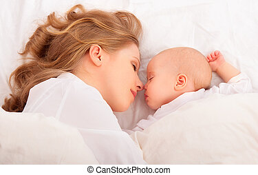 sleeping together. mother embraces the newborn baby in bed -...