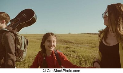 happy family slow motion video walking on nature boy girl and mom in a field on trekking trip. tourists with a guitar backpacks traveling. happy family travel tourism lifestyle concept
