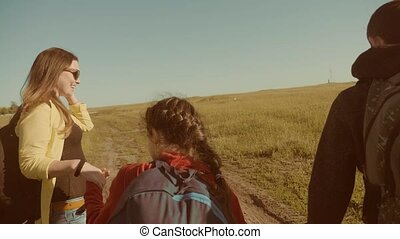 happy family slow motion video walking on nature boy girl and mom in a field on trekking trip. tourists with backpacks lifestyle traveling. happy family travel tourism concept
