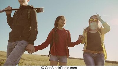 happy family slow motion video walking on nature boy girl and mom in a field on trekking trip. tourists with lifestyle a guitar backpacks traveling. happy family travel tourism concept
